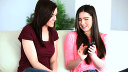 Women sitting on couch and using a mobile phone Footage