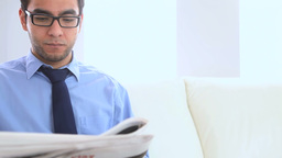 Businessman reading a newspaper on a couch Footage