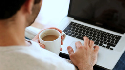 Man drinking a coffee while using his laptop Footage