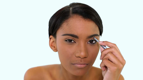 Woman plucking eyebrow with tweezers Live Action