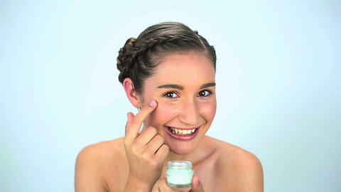 Young woman applying cream on her face Footage