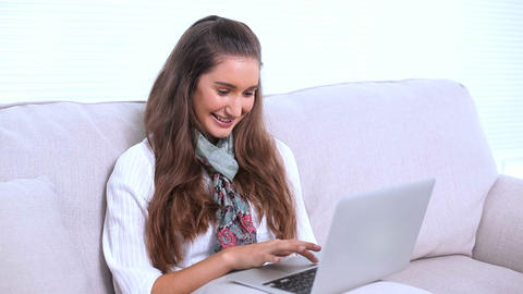 Smiling brunette using her laptop on sofa Footage
