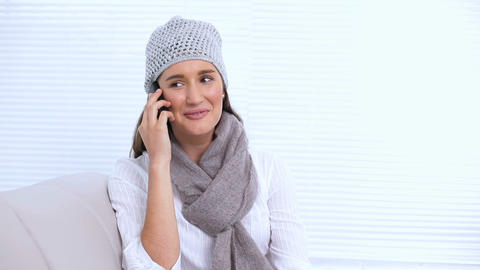 Smiling young woman with hat and scarf calling som Footage