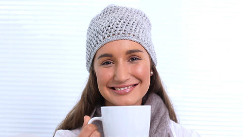 Young woman with hat and scarf smelling her cup Footage