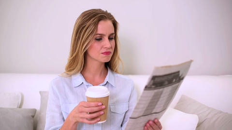 Woman reading newspaper and drinking coffee Footage