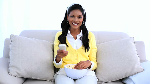 Smiling woman sitting on sofa changing channel of  Footage