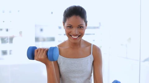 Beautiful woman holding dumbbells Footage