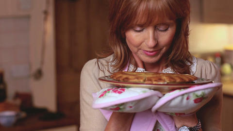 Mature woman smelling a pie she has just cooked Footage