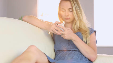 Beautiful teen sending a text message on her sofa Footage
