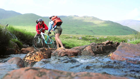 Couple crossing a stream together with their bikes Footage