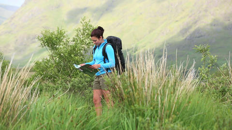 Active woman hiking on her own reading a map Footage