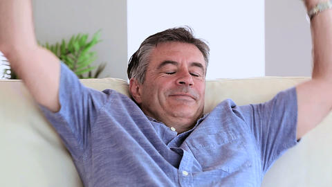 Smiling mature man relaxing on his couch Footage