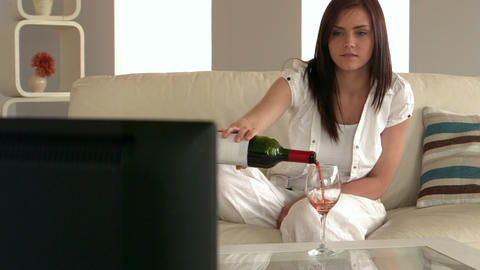 Young woman watching television and pouring glass  Footage