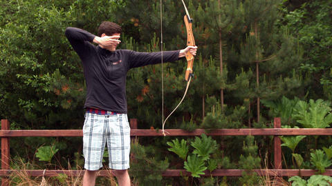 Athletic man shooting a bow and arrow Live Action