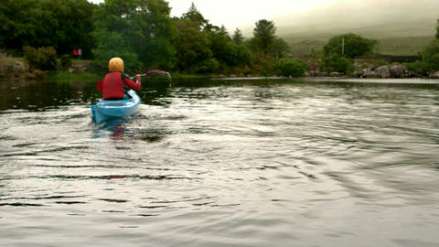Woman kayaking in a lake in the countryside Footage