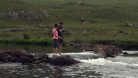 Couple standing on rocks in the middle of a flowin Footage
