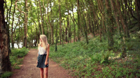 Attractive happy blonde walking on pathway through Footage