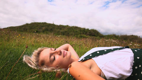 Attractive happy blonde lying down on lawn Footage