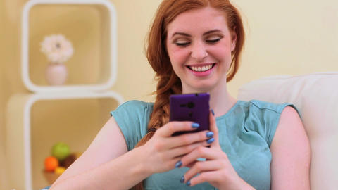 Beautiful brunette smiling and texting on smartpho Footage