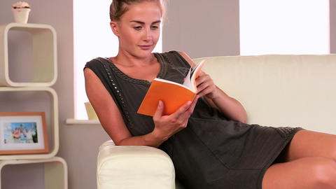 Attractive woman sitting on couch reading Footage