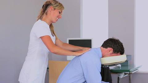 Masseuse giving businessman a shoulder massage Footage