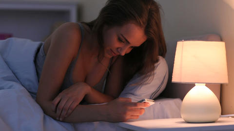 Pretty smiling brunette lying in bed texting on sm Footage