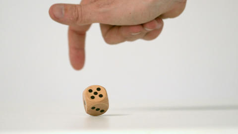 Hand letting twist a wooden dice Live Action