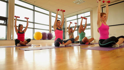 Fitness class and instructor exercising with dumbbells Footage