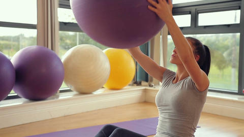 Sporty brunette woman lifting exercise ball Footage