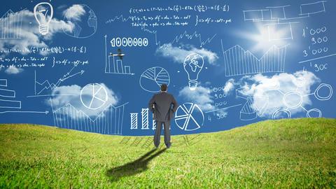 Businessman standing in grass watching statistics Animation
