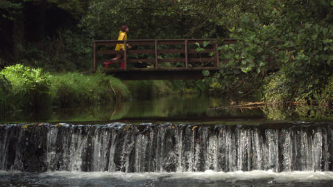 Video of idyllic waterfall with brunette running o Footage