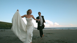 Happy newlywed couple running on the beach Live Action
