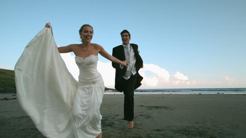 Happy newlywed couple running on the beach, Live Action