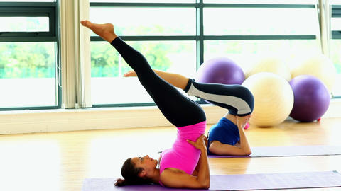 Fit slender women practising yoga on exercise mats Footage