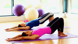 Toned women doing sports exercise lying on exercise mats Live Action