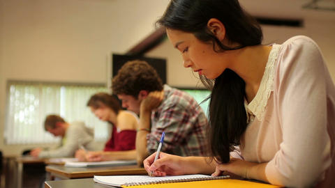 Attentive students sitting an exam in a classroom Footage