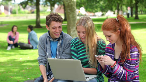 Three students using laptop together and laughing Footage