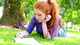 Student lying on the grass making notes Footage