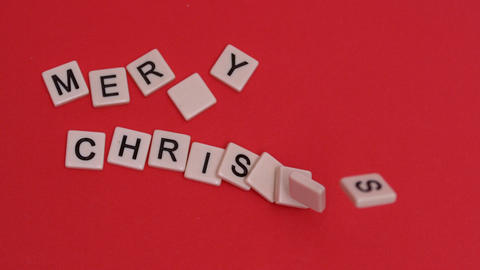 Letter tiles moving to spell out merry christmas on red background Live Action