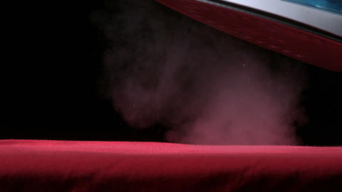 Iron releasing steam above a red cloth Footage
