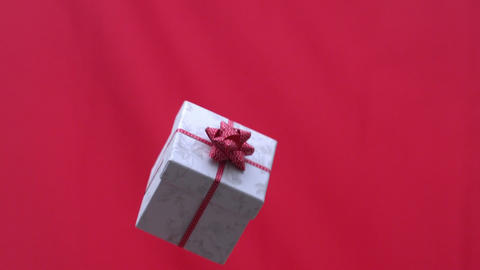 Christmas present tossed into the air on red background ビデオ