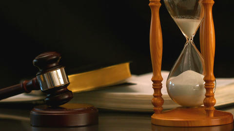 Sand flowing through hourglass beside gavel and bible Footage