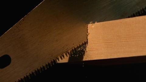 Saw cutting through wood on black background Footage