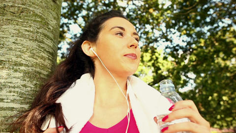 Fit brunette drinking water after her jog Footage