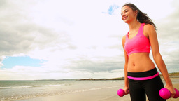 Smiling brunette lifting dumbbells on the beach Footage