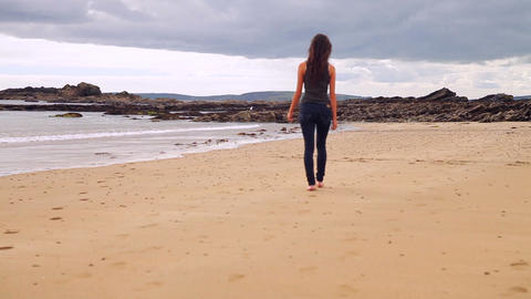 Beautiful brunette walking along the water by the  Footage