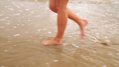 Woman Walking Along The Tide stock footage