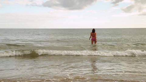 Energetic fit brunette running into the ocean Footage