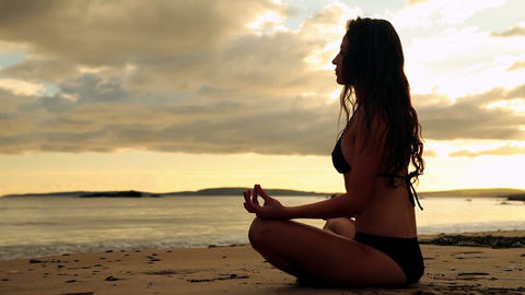 Gorgeous brunette meditating on the sand at sunset Footage