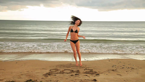 Gorgeous brunette dancing around with 2013 written in the sand Live Action
